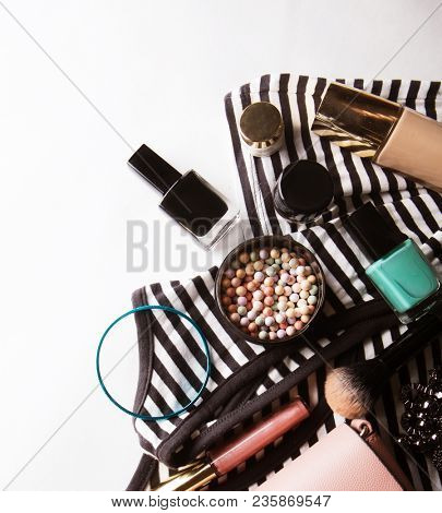 Stylized feminine flatlay with glasses, foundation,  lip gloss,  powder,  brush, handbag, striped shirt  isolated on white top view. Woman accessories from above copy space for text.