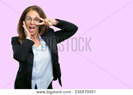 Middle age business woman looking at camera through her fingers in victory gesture winking the eye and blowing a kiss