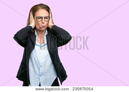 Middle age business woman covering ears ignoring annoying loud noise, plugs ears to avoid hearing sound. Noisy music is a problem.