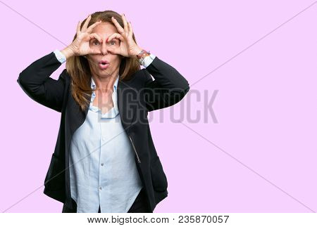 Middle age business woman looking at camera through her fingers in ok gesture. Imitating binoculars