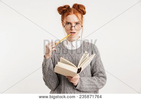 Portrait of a pensive young school nerd girl holding book isolated over white background