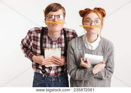 Funny couple of school nerds grimacing while holding notepads and pencils isolated over white background