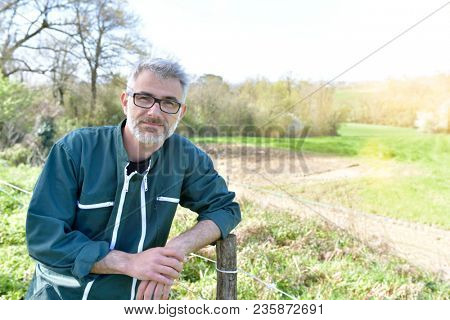 Portrait of farmer standing in agricultural field