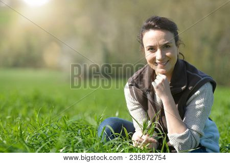 Farmer woman in agricultural field checking crops