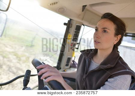 Farmer woman driving tractor