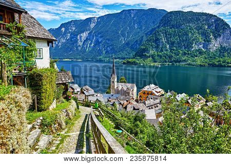 Hallstatt Austria vintage architecture and old houses in picturesque austrian mountains Alps on lake Hallstattersee. Paved stone walking track among green trees.