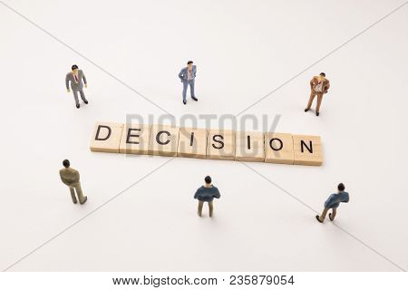 Miniature Figures Businessman : Meeting On Decision Word By Wooden Block Word On White Paper Backgro