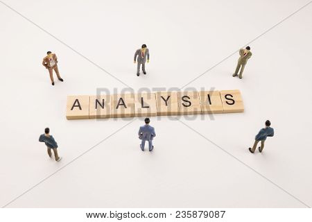 Miniature Figures Businessman : Meeting On Analysis Word By Wooden Block Word On White Paper Backgro