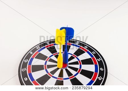 Blue And Yellow Dart Arrow On Center Of Dartboard On White Background, In Concept Of Opportunity And