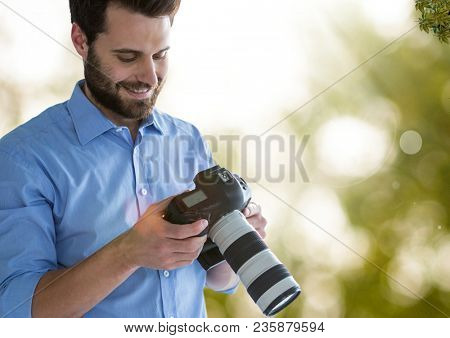 photographer looking the images on the camera. Green and white blurred lights and flares background
