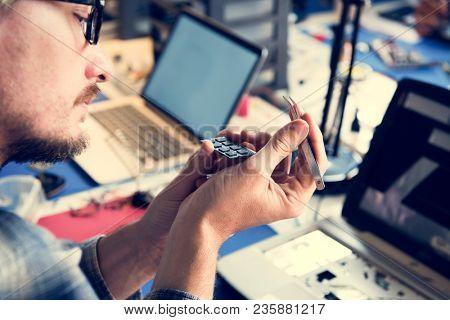 Closeup of hands holding tweezer with computer processor chips