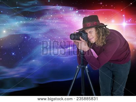Photographer taking picture in front of colored lights background