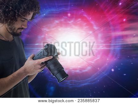 Photographer looking at his camera with lights on background