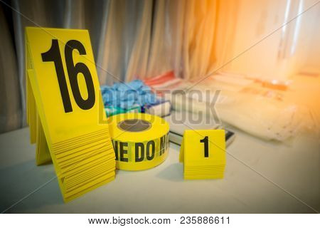 Police Line And Evidence Marker With Forencsic Science Tool Background On Table For Crime Scene Conc