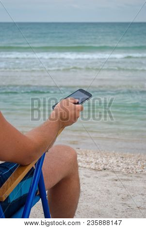 Young Man Sitting On Lounge On The Shore Holds In Hand Mobile Phone Gadget Resting Sunbathing, Looks