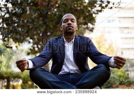Young American African Businessman In Informal Clothes Meditating In Lotus Pose Taking A Deep Breath