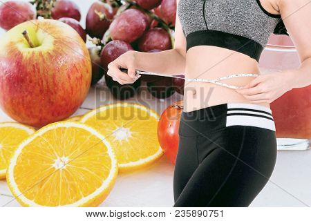 Woman Slim Measuring Her Waist Using A Tape Measure On Fresh Fruits Background - Healthy Eating