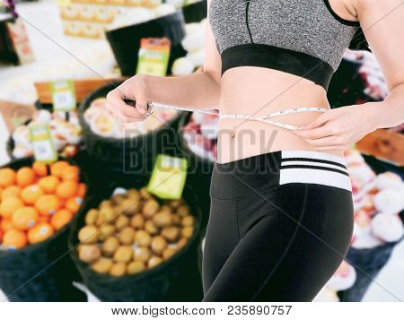 Woman Slim Measuring Her Waist Using A Tape Measure On Fresh Fruits In Supermarket Blurred Backgroun