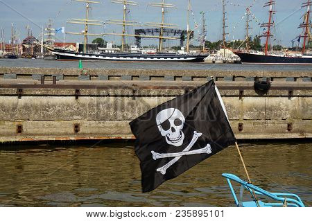 Black Pirate Flag Flying Form The Top Of A Mast On A Boat In The Port