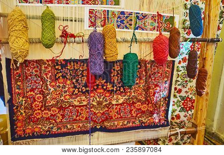 Hand Weaving Loom With Examples Of Colored Woolen Yarns  And Traditional Persian Carpet, Covered Wit