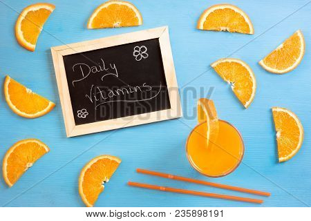High Angle Image Of A Blackboard With The Message Daily Vitamins, Surrounded By Slices Of Orange, A