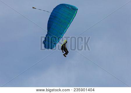 Parachutist With Blue Parachute Against Blue Sky Preparing For Landing