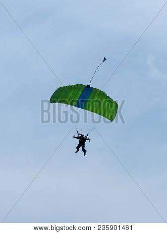 Parachutist With Green Parachute Against Blue Sky Preparing For Landing