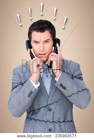 Frustrated business man with phones against cream background and exclamation points