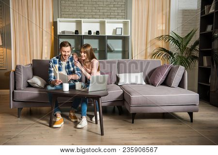Young Couple Sitting On Couch And Reading Book In Living Room
