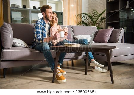 Side View Of Male With Girlfriend Sitting On Couch With Cups And Watching Laptop In Modern Living Ro