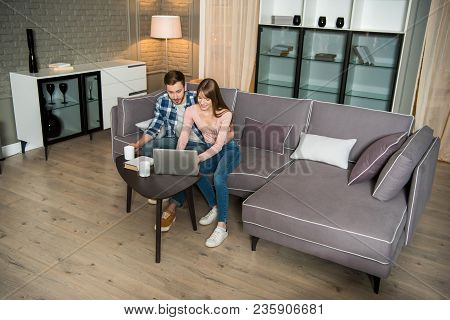 High Angle View Of Happy Couple Sitting On Couch And Using Laptop In Living Room In Modern Design