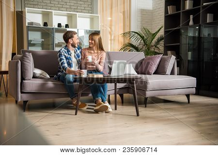 Young Couple Sitting On Couch With Cups In Living Room With Modern Design