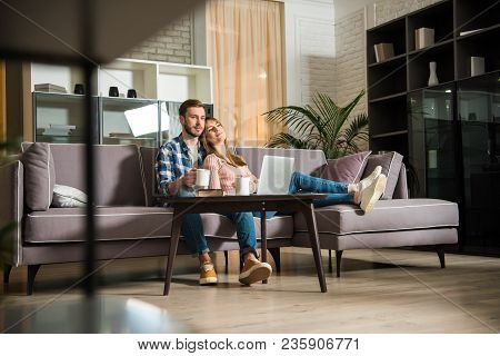Surface Level View Of Couple Watching Laptop In Living Room With Modern Interior