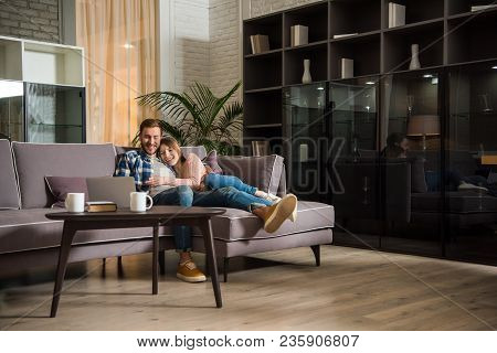 Couple Having Fun While Watching Laptop In Modern Living Room