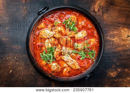 Traditional Creole cajun court bouillon with fish and seafood gumbo chowder stew as top view in a pot with copy space