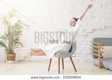 Beautiful Happy Young Female Waking Up In The Morning And Stretching In Blue Armchair, Holding Cup O