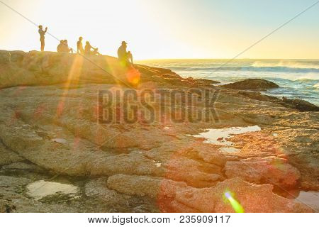 Unidentifiable People On The Rocks Of Noordhoek Beach Near Cape Town, South Africa, At Sunset. Touri