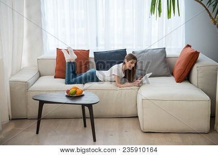 Side View Of Young Female Lying On Couch And Using Digital Tablet In Living Room With Modern Interio