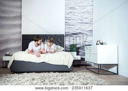 Smiling Couple Talking And Lying On Bed In Cozy Bedroom With Modern Interior