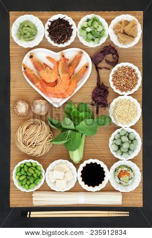 Japanese health food with seafood, udon noodles, sushi, miso and wasabi paste, tofu,  vegetables, soy, with foods high in omega 3, protein, antioxidants, vitamins and minerals. On bamboo and slate.