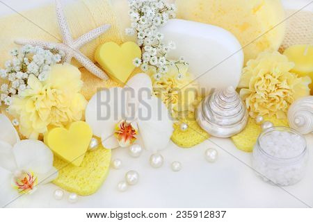 Bathroom beauty cleansing products with orchid and carnation flowers, yellow  heart shaped soaps, sponges, ex foliating scrub and wash cloths with decorative seashells and pearls on white wood.