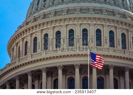The American Flag With Us Capitol In The Backround At Washington Dc.