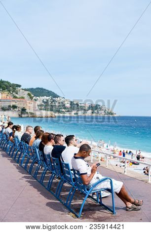 NICE, FRANCE - JUNE 4, 2017: People at the famous Promenade des Anglais in Nice, in the French Riviera, France, sitting in the characteristic blue chairs facing the Mediterranean sea