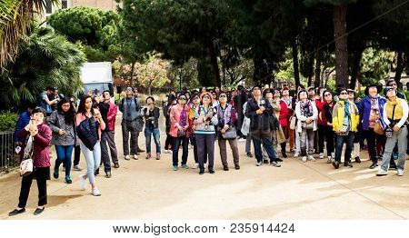 BARCELONA, SPAIN - APRIL 6, 2018: A large group of tourists admiring and taking pictures of the famous La Sagrada Familia in Barcelona, Spain, the impressive cathedral designed by Gaudi