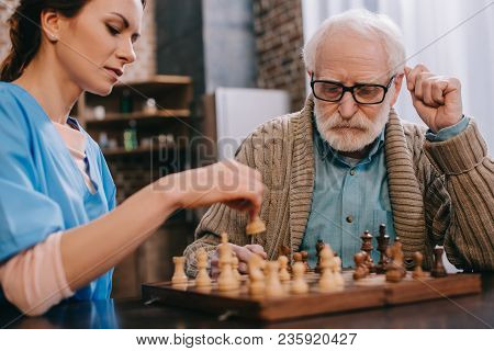 View Of Nurse And Senior Man Playing Chess