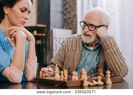 Thoughtful Nurse And Elder Man Playing Chess