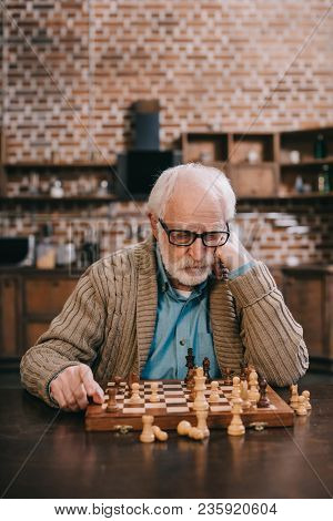 View Of Thoughtful Elder Man By Chess Board