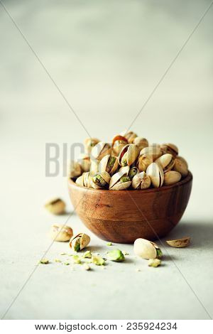 Green Salted Pistachios In Wooden Bowls On Light Concrete Background. Copy Space For Your Text. Heal