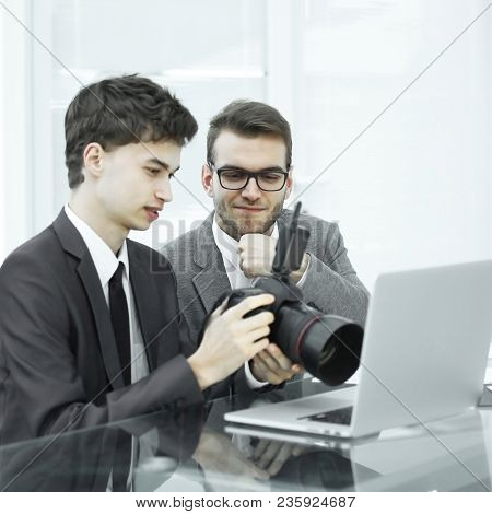 Two Qualified Photographers Choose A Photo To Upload Files To Their Laptop