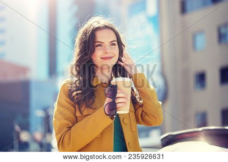 drinks and people concept - happy young woman or teenage girl drinking coffee from paper cup on city street